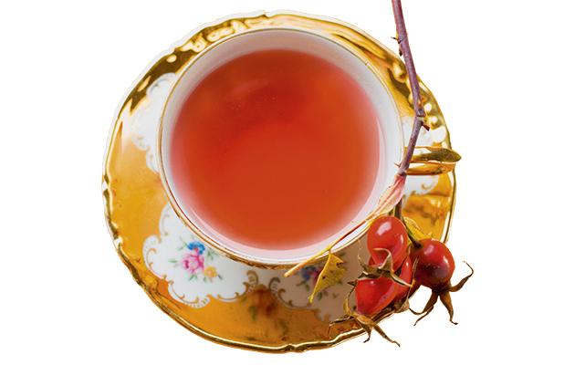 Rose hip tea incup fresh rose hips on